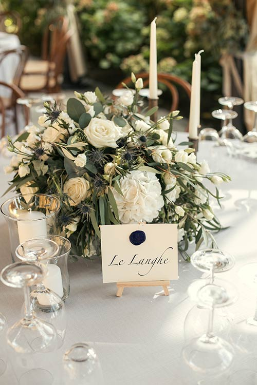 Centerpieces with olive leaves, white flowers and lot of country greenery