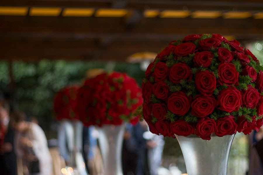 Large vases of red roses balls on the welcome aperitif buffet tables welcomed guests