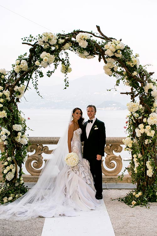 The majestic floral arch made by branches, ivy and bunches of white roses and peonies.