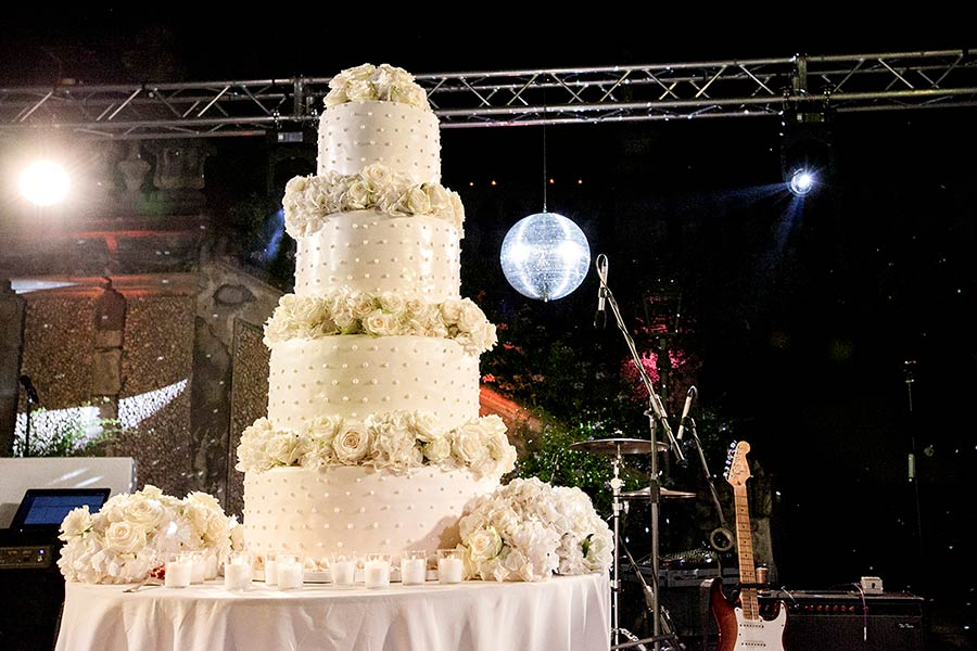 A huge white four tiered cake with white peonies and roses!